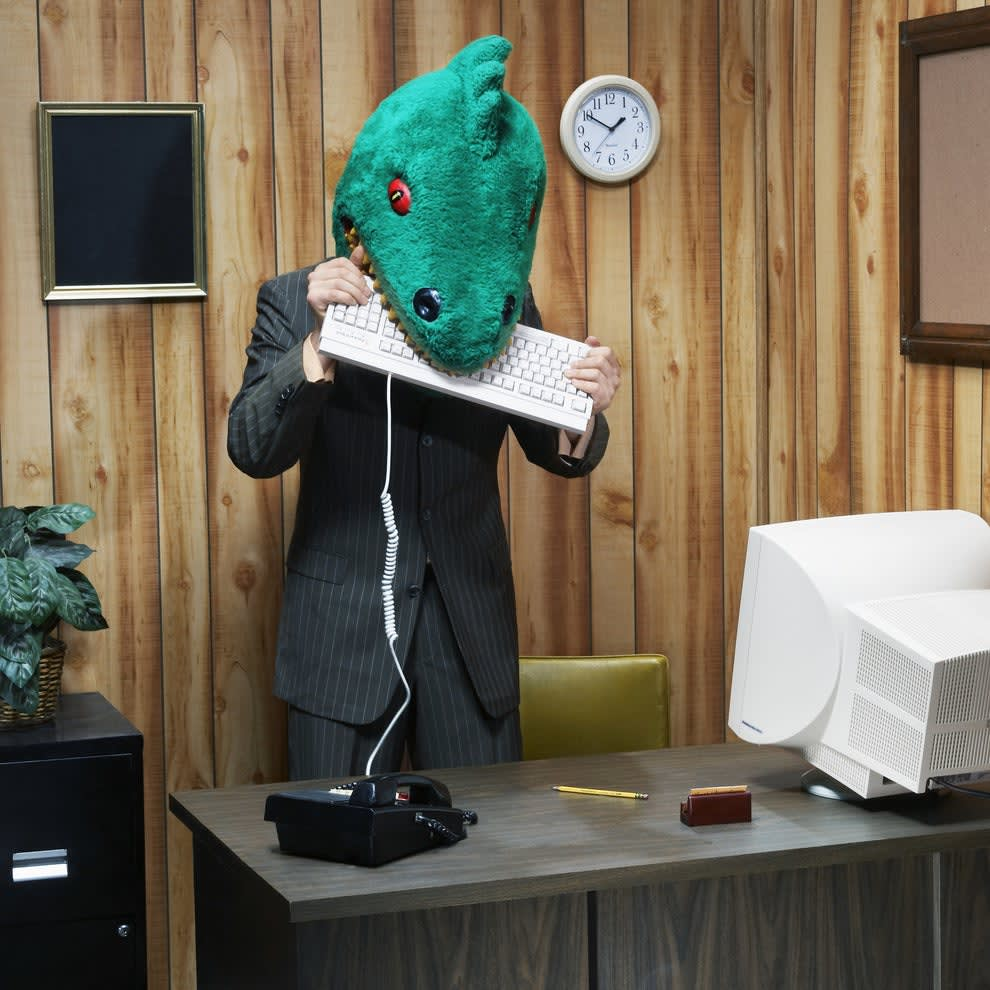 business person in a lizard mask biting a keyboard