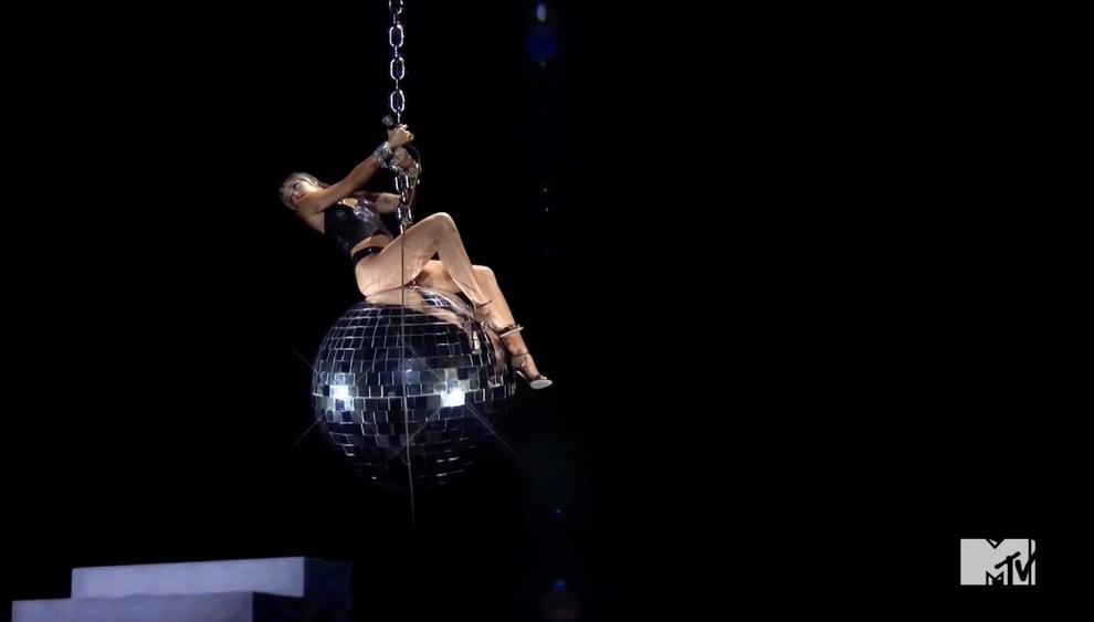 """Miley em cima da bola de espelhos na pose do vídeo de """"Wrecking Ball"""""""