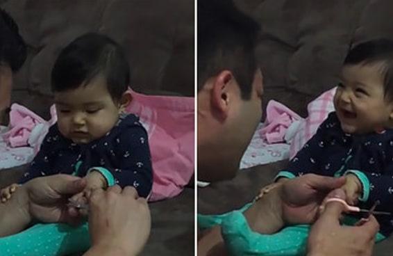 Veja uma bebê enganar o pai ao fingir que está chorando quando ele tenta cortar suas unhas