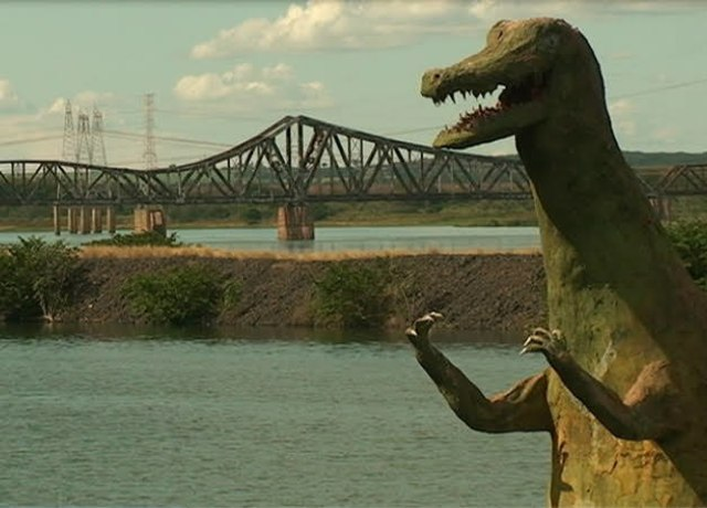 Estátua Dinossauro em frente a um rio ele tem as duas patinhas em frente ao peito, como se estivesse pronto pra briga
