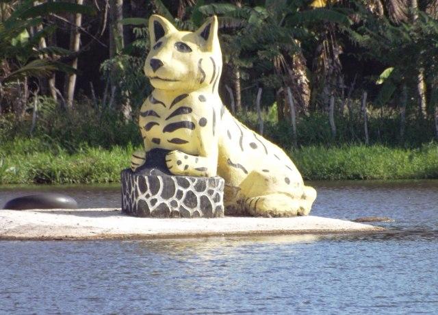 Escultura também nada realista de um gato amarelo gigante, no meio de um rio