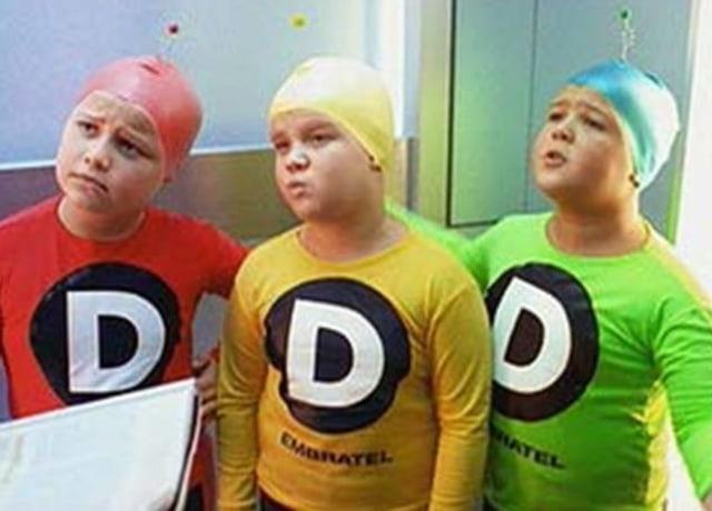 """três meninos, cada um com camisas longas e toucas de natação com uma antena. Cada um usa as roupas de uma cor: o primeiro vermelho, o segundo amarelo, e o terceiro verde. Todos tem um """"D""""no meio da camisa, com o logo da embratel abaixo."""