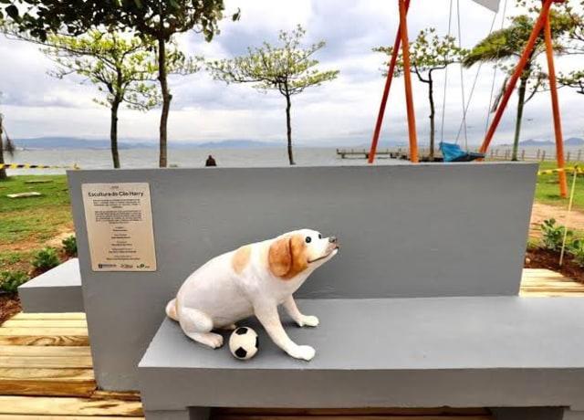 Escultura de um cachorro, não muito realista, em cima de um banco - com uma bolinha de futebol.