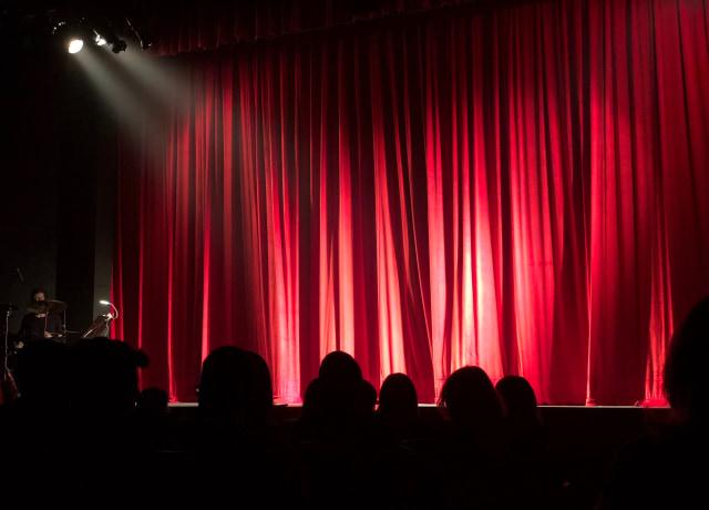 Um teatro com cortinas vermelhas no palco