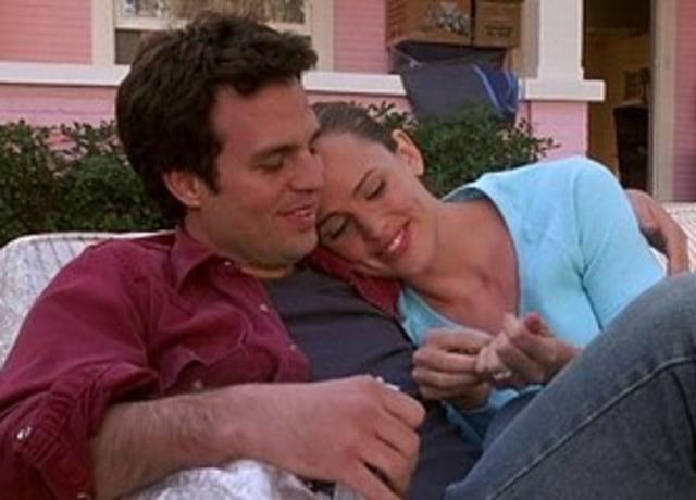 Jenna e Matt compartilhando um doce na parte externa da casa.