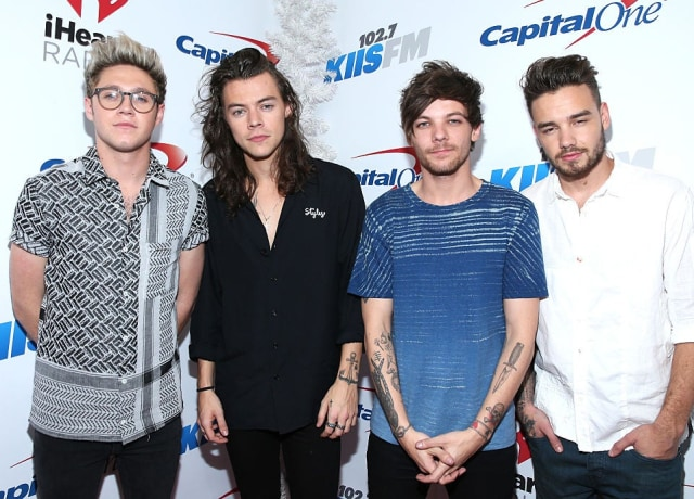 Niall Horan, Harry Styles, Louis Tomlinson, and Liam Payne smile backstage at Jingle Ball 2015