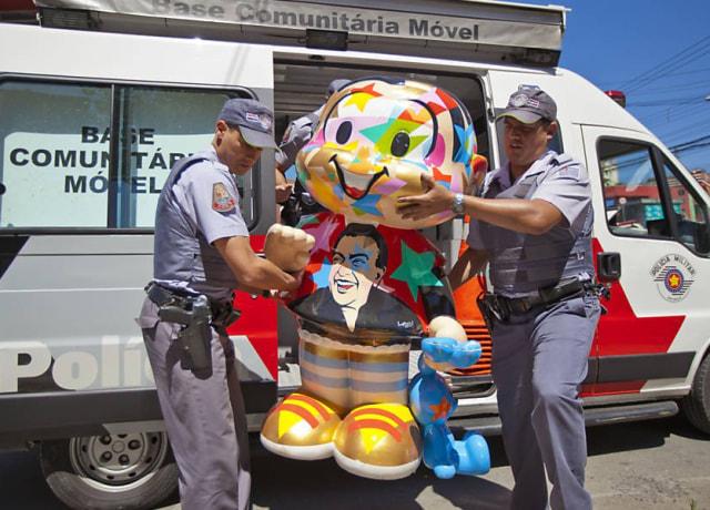Estátua da mônica sendo carregada para dentro do camburão, por dois policiais militares