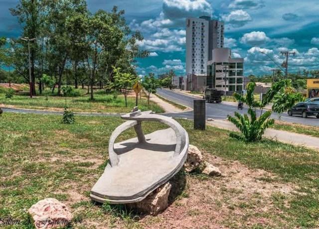 Chinelo gigante, parecendo ser feito de concreto, no meio de uma praça