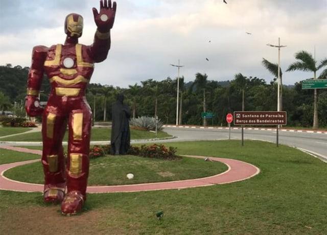 Estátua completamente desproporcional do Homem de Ferro, aparentando ter mais de dois metros, no meio de uma praça.