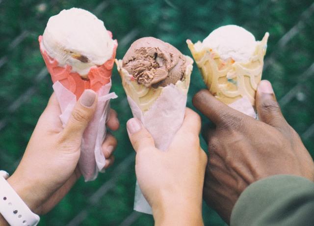 Três mãos segurando sorvetes