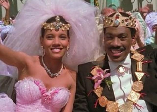 Akeem e Lisa com roupas da realeza acenando em um desfile.