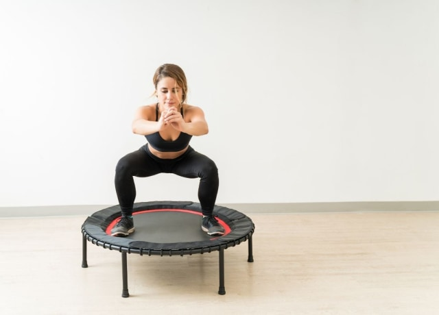 A woman exercising on a trampoline