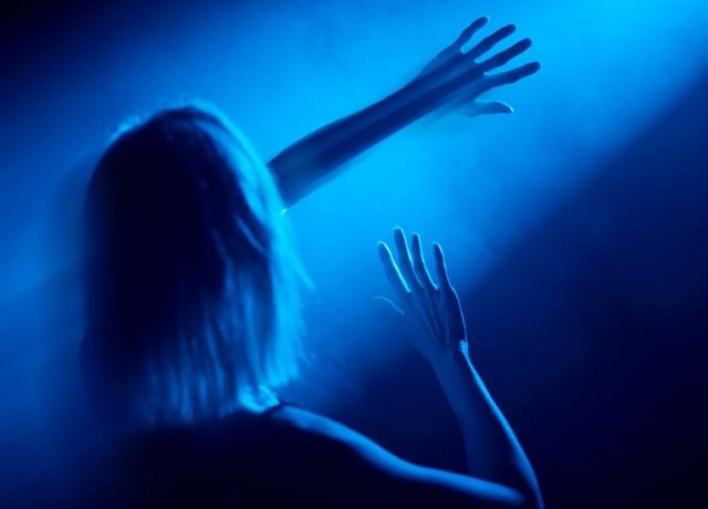 Uma mulher no escuro se protegendo de um faixo de luz