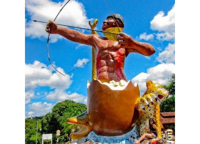 Estátua de um índio saindo de dentro de um cupuaçu, com uma onça do lado