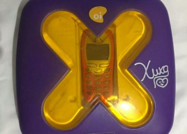 Celular de 2003, em uma caixa roxa com um X transparente amarelado, que permite ver o aparelho mesmo dentro do recipiente