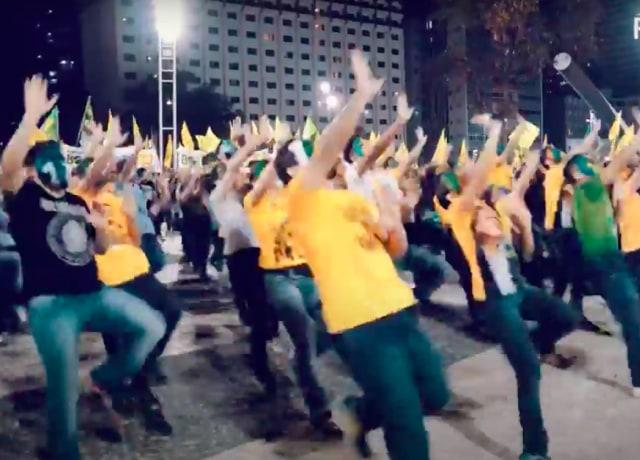 Pessoas dançando com as palmas das mãos paralelas ao céu