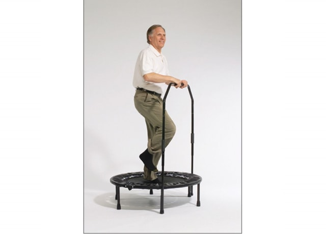 Older man jumping on a trampoline with little enthusiasm