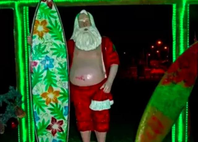 papai noel sem camisa e uma prancha de Surf