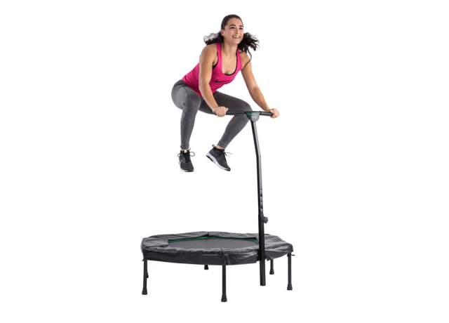 Girl smiling as she hops on a teeny tiny trampoline