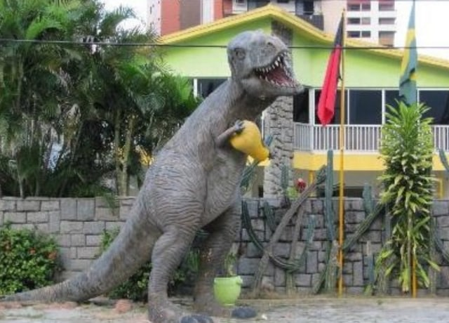 Tiranossauro segurando um caju