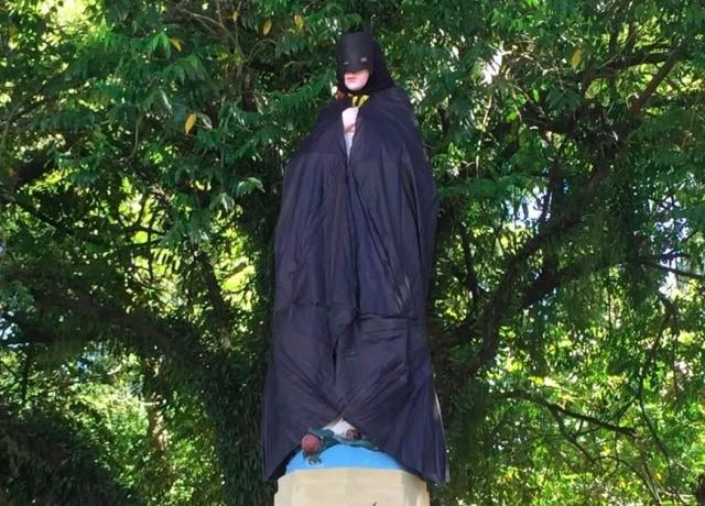 Estátua de Nossa Senhora, com uma capa e uma máscara do Batman, colocados por cima da escultura