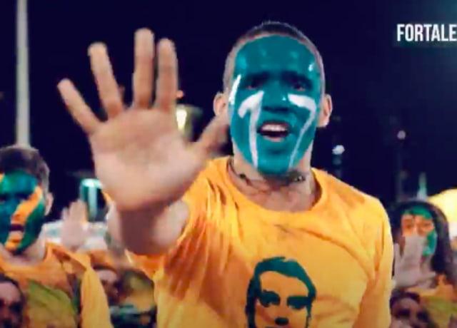 """Homem com a cara pintada de verde, fazendo sinal de """"pare""""com a mão, enquanto usa uma camiseta amarela com o rosto de bolsonaro"""