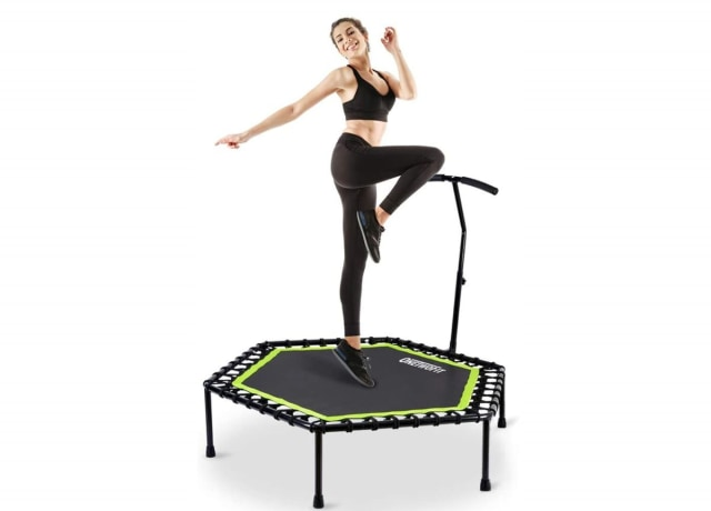 A happy woman doing some fun stretches on a tiny trampoline