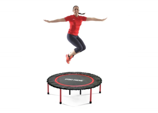 Excited woman jumping on a mini trampoline