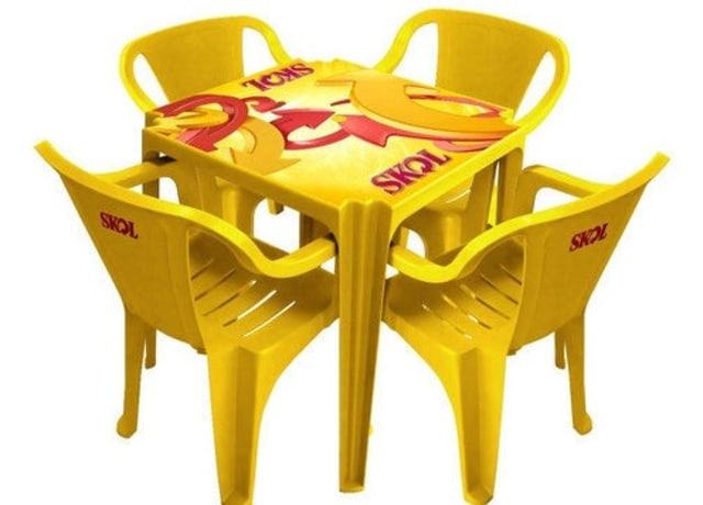 Mesa e cadeiras de plástico amarelo com estampa da cerveja Skol
