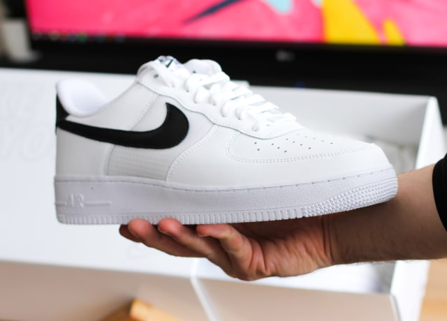unpaired white and black Nike Air Force 1 low-top shoe