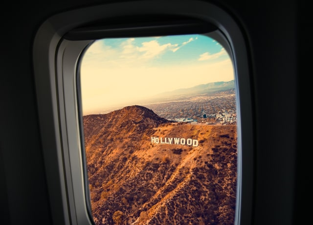 person inside plane looking hollywood freestanding letter at daytime