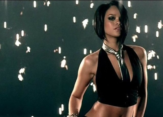 Rihanna clad in a top with a tie, with flares in the background
