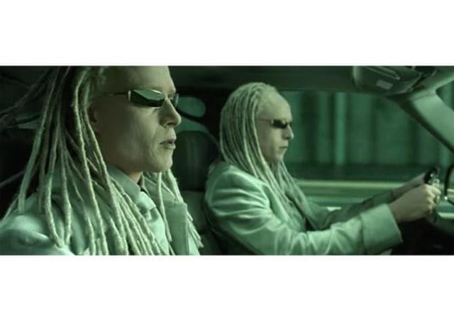 Imagem do filme, os Irmãos Fantasma vestem branco e estão dentro de um veículo em movimento, um ao lado do outro.