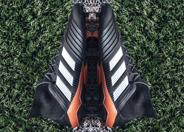 pair of black Adidas cleats on grass field