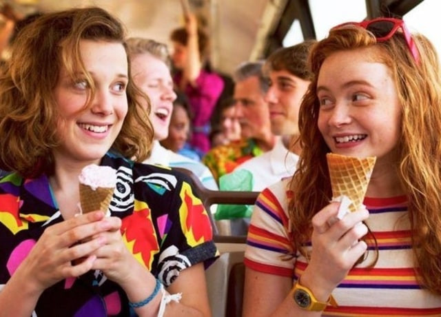 Eleven and Max smile at each other while holding melting ice cream cones up to their faces.