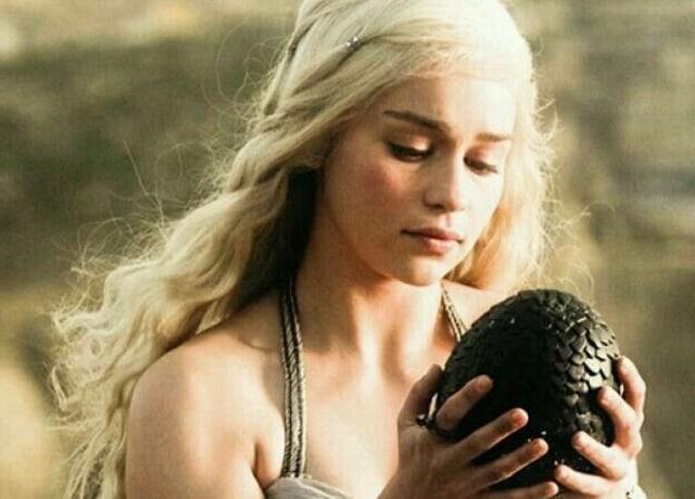 """Imagem da série """"Game of Thrones"""", mostra a personagem Daenerys Targaryen segurando um ovo de dragão em suas mãos. A casca do ovo tem cor escura e textura."""