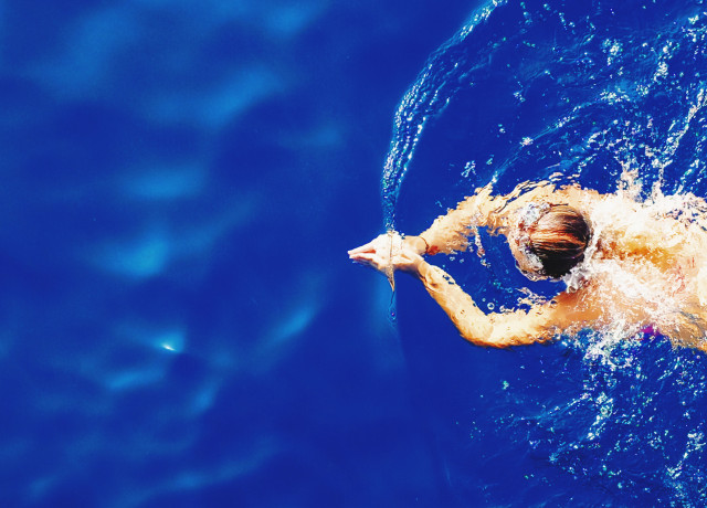 close-up photography of woman swimming on calm water