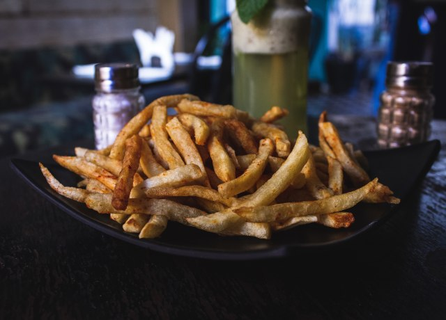 potato fries on black ceramic plate on top of wooden table