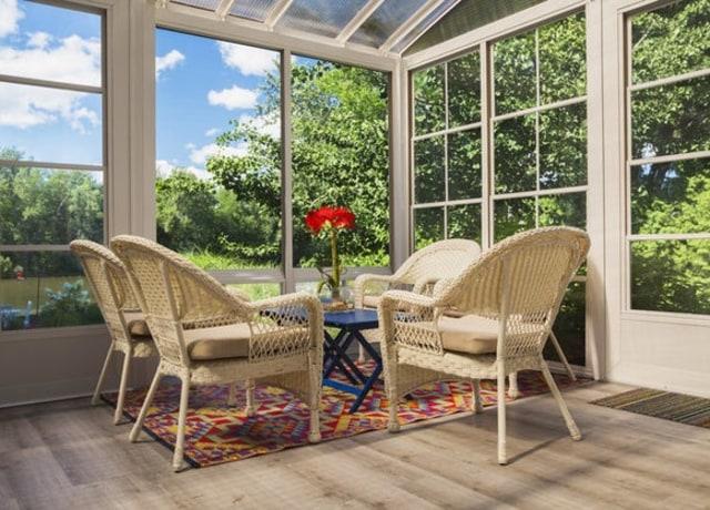 Uma sala externa com janelas e cadeiras de jardim