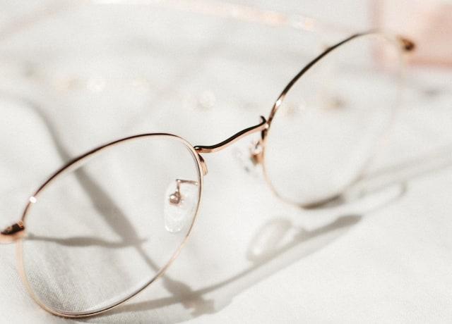 silver framed eyeglasses on white textile