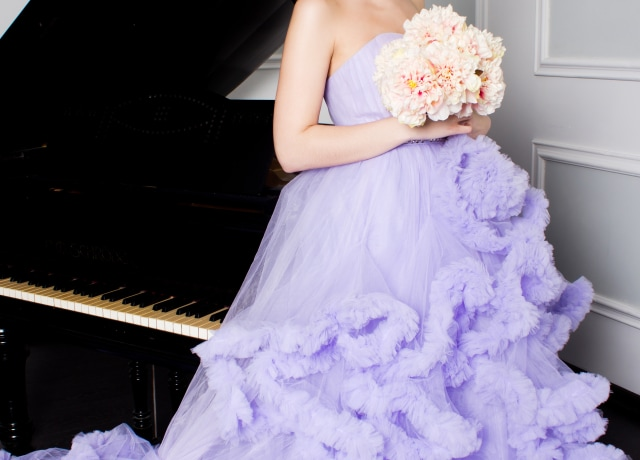 woman in purple off-shoulder dress holding bouquet of flowers