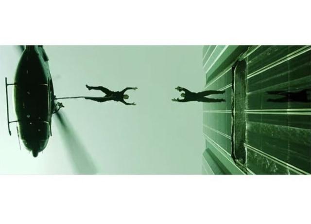 Imagem do filme, Neo, preso a uma corda, se joga de um helicóptero para pegar Morpheus, que se joga de um prédio.