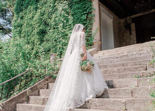 bride walking on stairway near garden