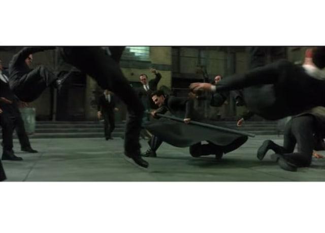 Imagem do filme, Neo no centro da imagem com uma barra de ferro nas mãos, lutando contra vários Agentes Smith ao mesmo tempo.