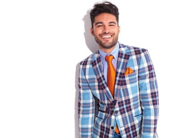 Foto de um homem usando um terno xadrez em tons azuis, com uma gravata laranja.