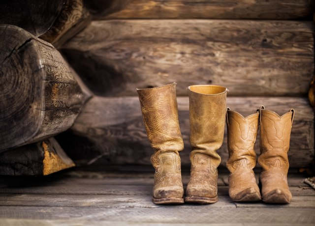 two pair of brown leather cowboy boots near brown log