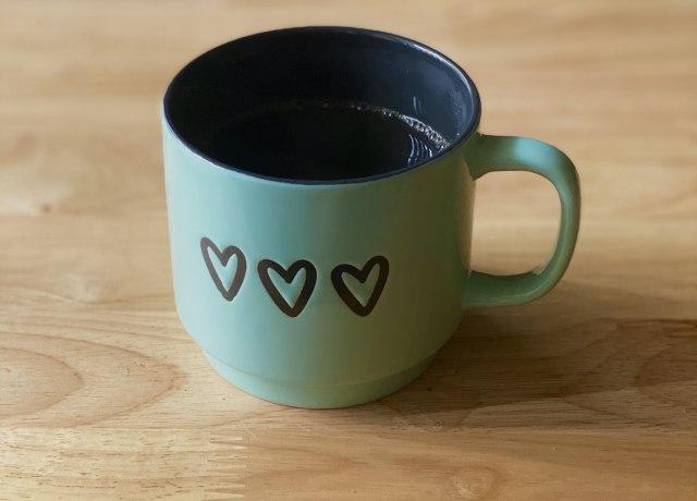 xícara verde de cerâmica com 3 corações