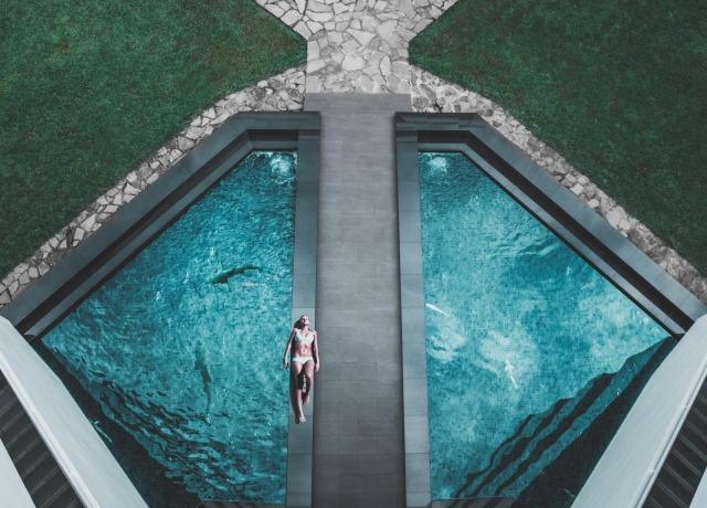 bird's eye view of woman lying on floor beside swimming pool