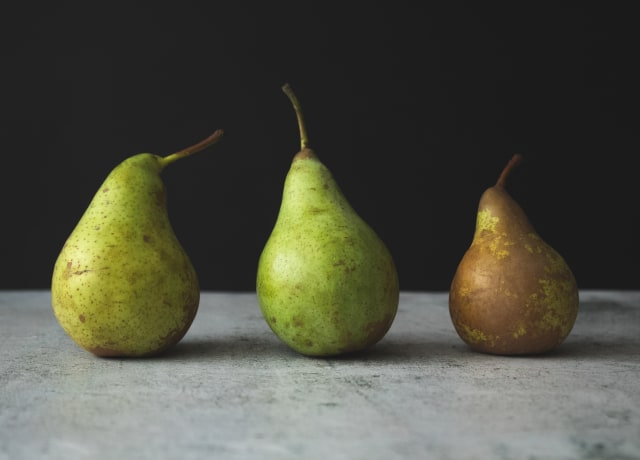 two green pear fruits on white textile