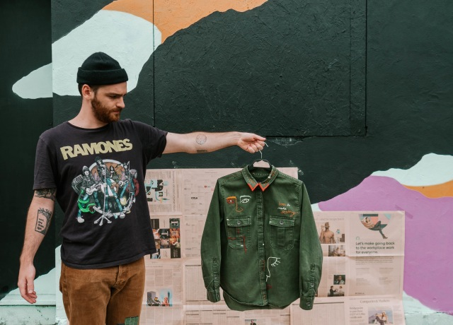 man in black crew neck t-shirt and brown pants standing beside wall